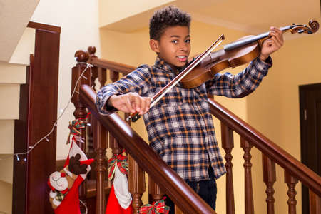 solo  christmas: Smiling afro kid plays violin. Boy playing violin on Christmas. Young violinists smile. True Christmas concert. Stock Photo