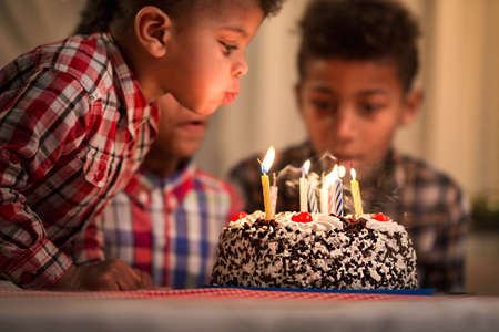 blows: Black toddler blowing candles out. Child blows birthday candles out. Youngest brothers birthday. Spending festive time together. Stock Photo