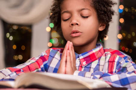 Afro child praying. Black kid prays beside window. Boys evening prayer. Gesture of faith. Banco de Imagens