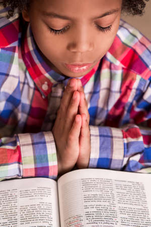 mulatto: Mulatto boy praying. Kid in shirt is praying. Young man with prayer-book. His faith is strong. Stock Photo