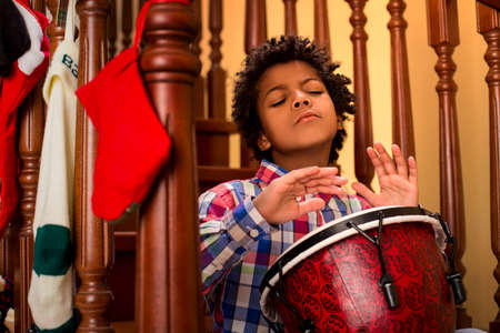 solo  christmas: Enthusiastic darkskinned boy playing drum. Kid plays drum on stairs. His inspiration is limitless. Let the music flow. Stock Photo