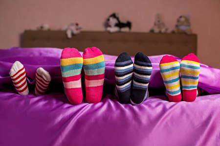 다채로운 양말에 어린이 발. 아이의 화려한 밝은 양말. 그들은 그들이 숨겨져 있다고 생각합니다. 숨바꼭질.
