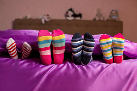 Children's feet in colorful socks. Kid's colorful bright socks. They think they're hidden. Hide and seek. Фото со стока
