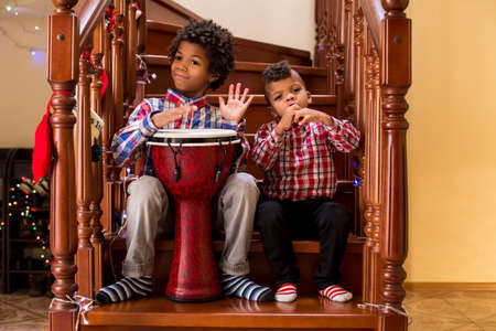 duet: Two afro boys play music. Kids playing music on stairs. Creative duet of young musicians. Starting a music tour. Stock Photo