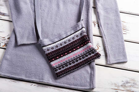 womans clothing: Womans gray purse with sweater. Purse and sweater on showcase. Casual collection clothing on display. Woolen handbag for ladies.