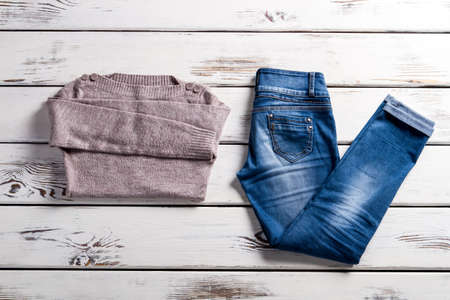 pullover: Bateau neckline sweater and jeans. Jeans and sweater on shelf. Blue jeans and beige sweater. Ladys clothes for cool weather.