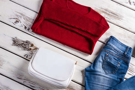 womans clothing: Sweater with handbag and jeans. Womans clothing laying on shelf. Clothes sale with discounts. Ladys garments in local store.