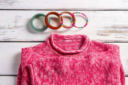 cuff bracelet: Pink wool pullover and bracelets. Bright pullover on store showcase. Close-up of bracelets and sweater. High-quality clothes in magazine.
