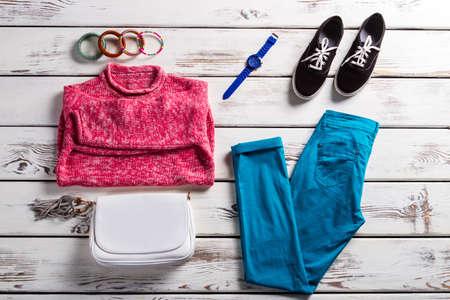 Lady's outfit met roze trui. Kleurrijke kleren op witte plank. Felgekleurde casual kleding. Vrouwelijke kleren en eenvoudige schoenen.