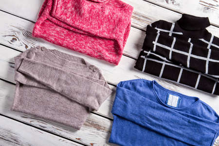 pullovers: Set of different female pullovers. Few pullovers laying on showcase. Clothing of different pattern. Merchandise from fresh catalog.
