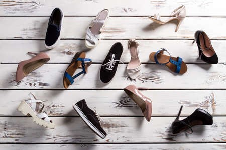 shoe shelf: Different shoes laying on floor. Ladys footwear on wooden background. Mess on shoe stores floor. Shoes fell from shelf. Stock Photo