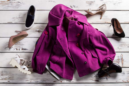 purple shoes: Crumpled purple coat and shoes. Coat with footwear on shelf. Mess in womans clothing store. Poor quality of clothes delivery.
