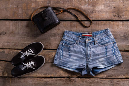 woman's clothing: Womans denim shorts with handbag. Retro clothing on wooden table. Summer sale at vintage boutique. Ladys classic clothes for summer.