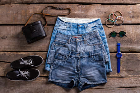 woman's clothing: Ladys denim shorts and accessories. Womans clothing on old floor. Small accessories with denim garments. Simple classic clothes and bracelets. Stock Photo