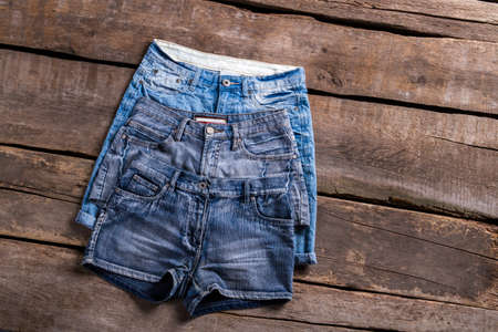 denim shorts: Pairs of different denim shorts. Womans denim shorts on table. Vintage clothes shops new arrivals. Classic shorts of different color.