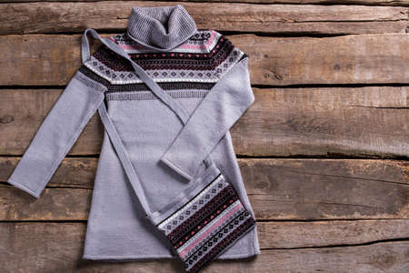tunic: Warm gray tunic with purse. Warm tunic on old floor. Gray tunic on brown shelf. Ladys garment on aged table. Stock Photo