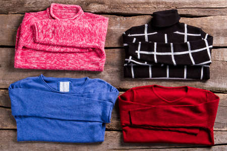 sweatshirts: Female sweatshirts of different colors. Sweaters on old wooden table. Colorful pullovers on wooden planks. Different sweatshirts at vintage store. Stock Photo