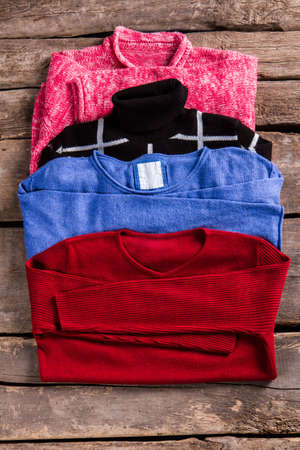 pullovers: Womans pullovers of different color. Pullovers on aged wooden floor. Vintage store showcase with pullovers. Stylish sweaters at retro shop.