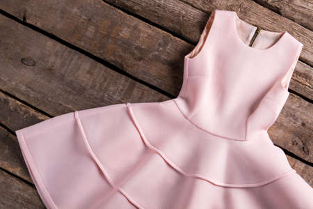 sleeveless dress: Light salmon dress with folds. Dress on old wooden background. Garment at vintage fashion house. Festive sleeveless dress. Stock Photo