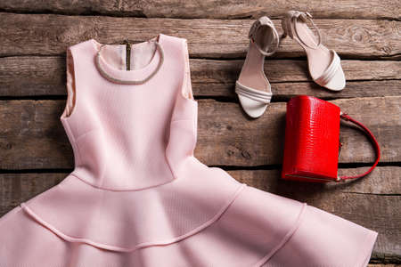 Jurk met ketting en portemonnee. Avond kledingstuk op oude plank. Vintage opslag showcase met kleren. Combinatie van kleding en sieraden.