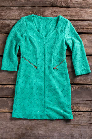 woman's clothing: Turquoise dress with zipper pockets. Tuquoise dress on old shelf. Garment on aged wooden background. Womans high-quality clothing.