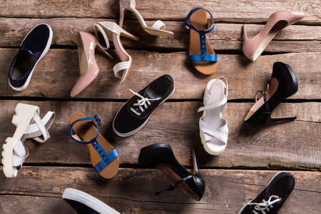 shoe shelf: Different female shoes on floor. Footwear on old wooden background. Shoes on retro boutique shelf. Mess on shoe stores floor. Stock Photo
