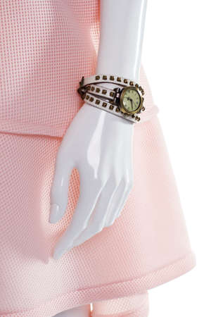 Classic watch on female mannequin. Female mannequins arm with watch. Vintage watch with leather strap. Round watch with white strap.