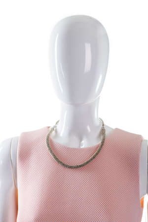 neckline: Necklace on mannequins neck. Female mannequin with delicate necklace. Salmon top and jewelry. Scoop neckline top with bijouterie.