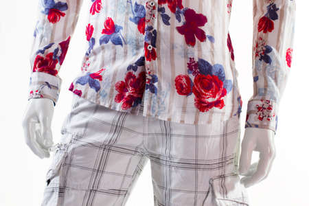 male mannequin: Shirt and shorts on mannequin. Male mannequin in summer apparel. Cargo shorts and floral shirt. Checkered shorts with cotton shirt.