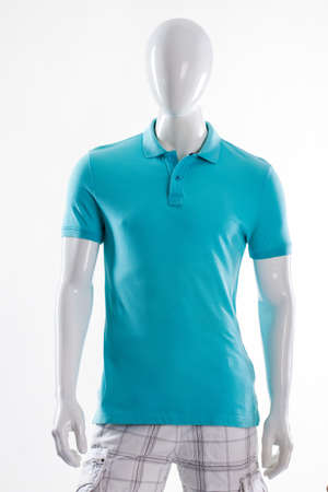 male mannequin: Blue polo t-shirt on mannequin. Male mannequin in fitted t-shirt. Mans t-shirt of bright color. Simple summer garment for men.