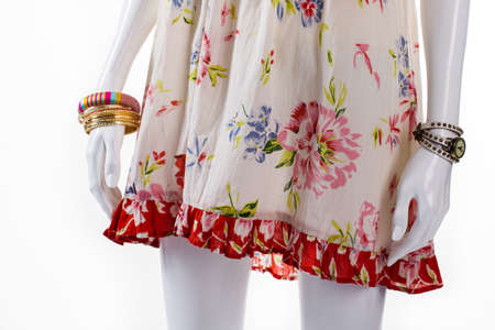 seson: Bracelet and watch on mannequin. Female mannequin with small accessories. Floral sarafan and bracelets set. New arrivals of clothing.