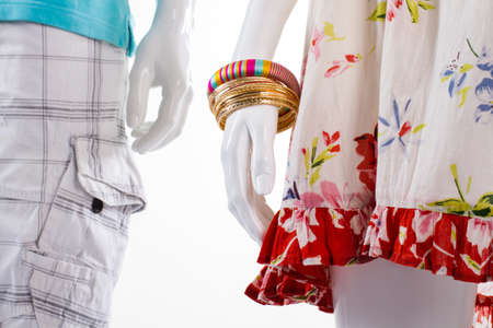 womans clothing: Bracelets and shorts on mannequins. Mannequins in light-colored clothing. Womans bracelets and mens shorts. Clothes and set of bracelets.
