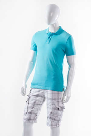 male mannequin: T-shirt and shorts on mannequin. Male mannequin wearing summer clothes. Blue t-shirt and white shorts. Cargo shorts with polo t-shirt. Stock Photo