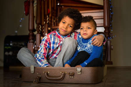 memorable: Two boys sitting inside suitcase. Two brothers sitting beside staircase. This is a memorable moment. Together all the time. Stock Photo