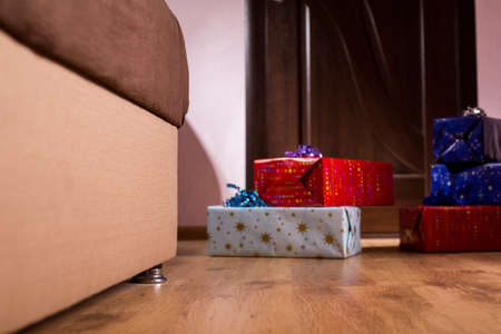 addressee: Pile of presents beside sofa. Birthday gifts in empty room. Where is the addressee. Boxes that bring joy.