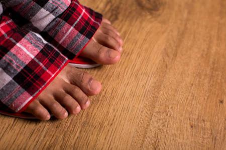los pies del niño afro en zapatillas. Primer plano de los pies en zapatillas. No caminar descalzo. Comodidad y facilidad.