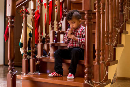 wind instrument: Mulatto child plays wind instrument. Boy playing flute during Christmas. Take your time, maestro. So young yet so skillful.