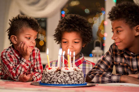 Afro boys and birthday cake. Three kids sitting beside cake. Make a wish now. Evening birthday celebration at home.