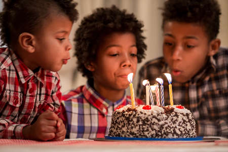 capture the moment: Three kids blowing candles out. Boys blow cakes candles out. Moment theyve been waiting for. Important part of the tradition. Stock Photo