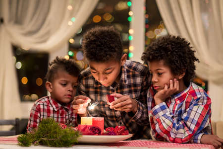 holiday lighting: Afro children lighting Christmas candles. Boys light candles on Christmas. Holiday preparations in the evening. Decorating room for Christmas. Stock Photo