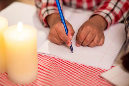 sudden: Child writes letter by candlelight. Boys hand writing by candlelight. Young poets revelations. Sudden flow of thoughts.