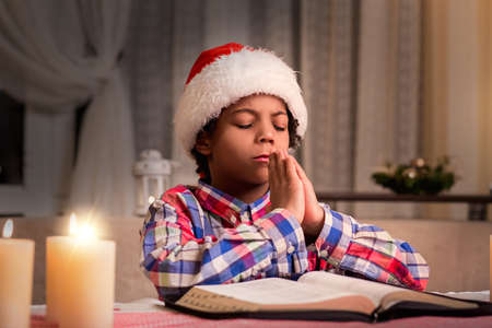 Darkskinned boy praying on Christmas. Little Santa prays to God. Purity of young soul. Prayer after reading Bible.