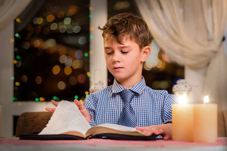 poems: Boy turning page of book. Child and book by candlelight. He read half of it. Huge collection of poems.