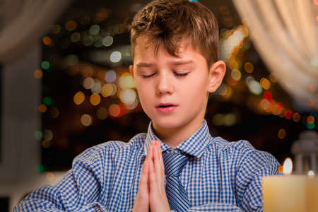Child praying out loud. Boy praying by candlelight. He speaks to the Lord. Young age but strong faith.