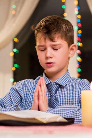holiday prayer book: Boy praying at the table. Kid prays at nighttime. Christmas prayer at city church. Youthful parishioner on Christmas.