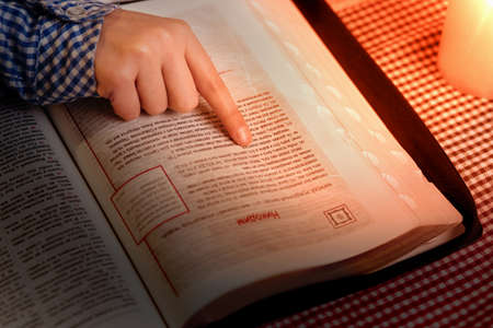 religious text: Kids hand on gospel book. Childs finger pointing at text. Reading throught another chapter. Studying religious text. Stock Photo