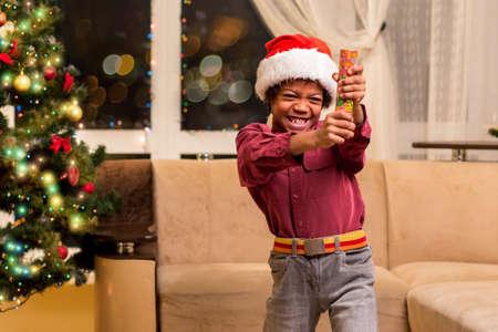 petard: Afro boy holding Christmas petard. Little Santa with fire cracker. It will be loud. Happy holidays, dear neighbours.
