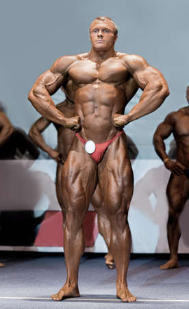 strongest: Athlete in lat spread pose. Bodybuilder showing muscles on stage. One of the strongest contenders. Becoming the champion.