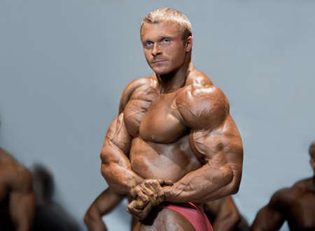 definition high: Man flexes chest and arms. Bodybuilder in front of competitors. Great muscle definition. High level bodybuilding competition.