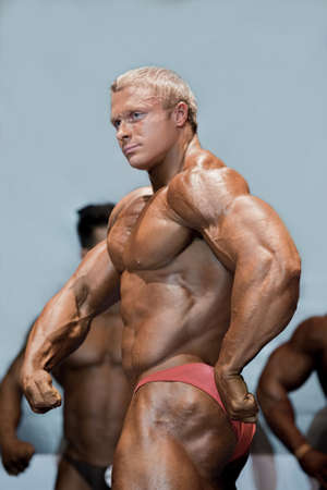 composure: Young bodybuilder in side pose. Male athlete posing on stage. Key moment of performance. Strength and composure. Stock Photo